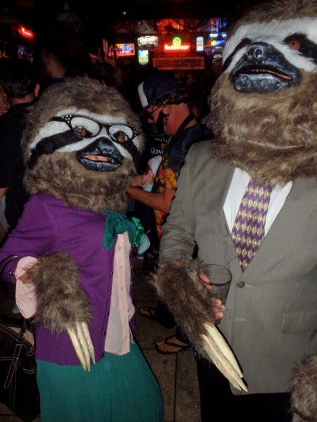 Люди в костюмах и масках танцуют на вечеринке