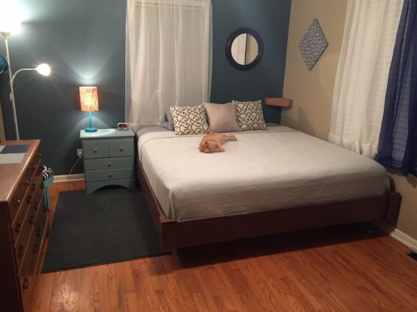 На мягкой кровати лежит рыжий кот
